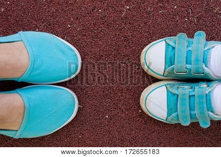 Female and child's feet in sports turquoise shoes. Sneakers are on the ground in a park close-up. Together. Family. Mother and son walking in the park.