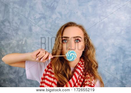portrait of pretty female with surprised face holding candy near her lips