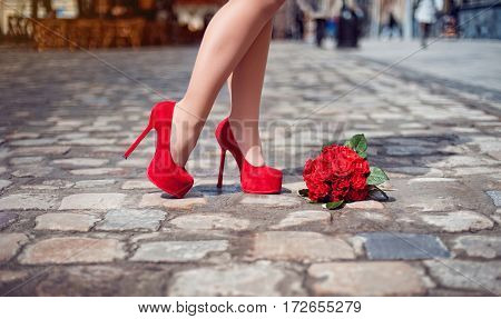 Close-up image of elegant feminine legs in red high heel shoes standing at street near red wedding bouquet with roses