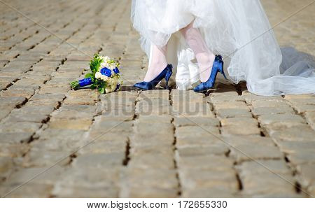 Close-up shot of elegant feminine legs in blue high heel shoes standing at street near blue and white wedding bouquet with roses