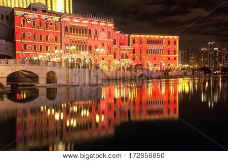 An abstract image of lights being projected onto the side of a building for a holiday display on the island of macau lit up at night in Asia reflecting off of water.