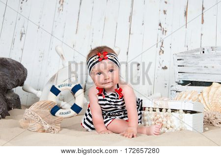 Cheerful little girl in a marine style sits on the sand on a background of white boards, a life buoy