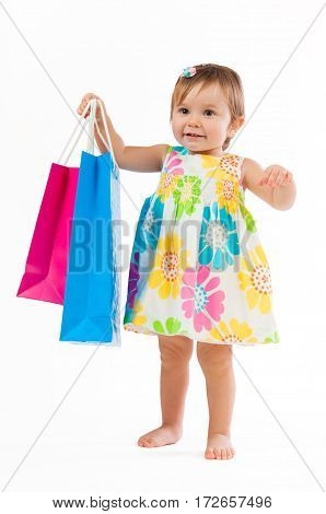 Little girl standing with colorful paper bags isolated on white background. Little fashion-girl.