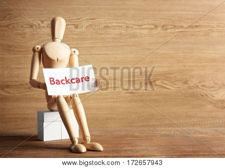Mannequin holding paper with word BACKCARE on wooden background
