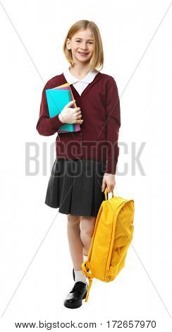 Cute girl in school uniform with backpack and books on white background