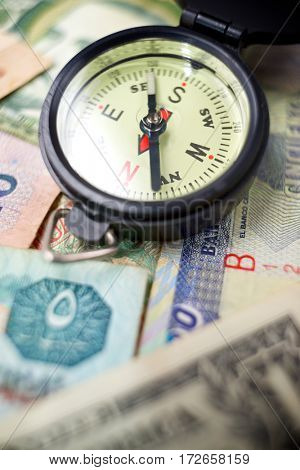 Compass and banknotes of different countries.
