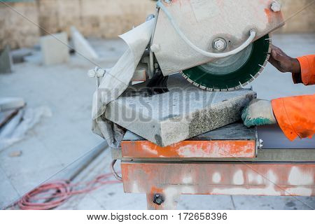 Machine has sharp blade which makes clean cut in stone or granite. It uses abrasive action to slice through material as the saw rotates at high speed. And man builder hands.