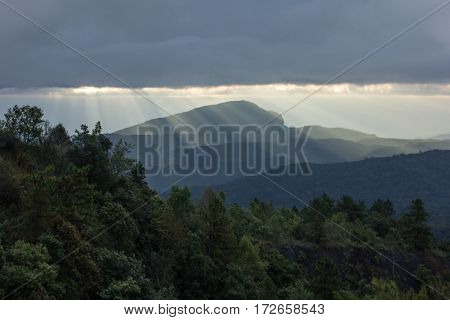 Sun rays over valley. Sun rays over hill. Tree in sun rays. Lonely tree. Tree with mountains in the background. Mountains in the background. Sunny clouds. Cloud eye. Dreamy landscape.