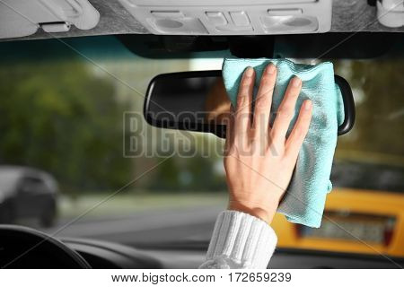 Closeup of woman cleaning a rear view mirror, inside view
