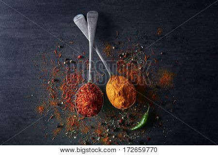 Spices in metal spoons on table