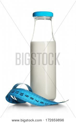 Milk diet concept. Bottle and measuring tape isolated on white