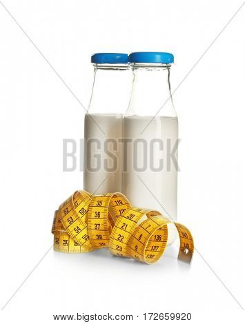 Milk diet concept. Bottles and measuring tape isolated on white