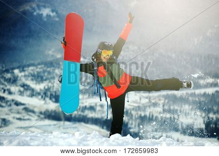 Beautiful young girl with a snowboard at winter resort
