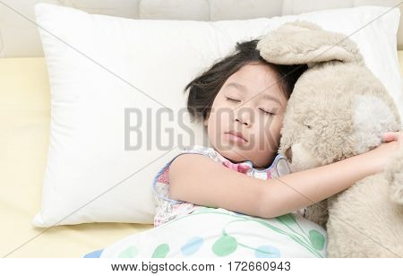 cute little asian girl sleep and hug teddy bear on bed in the bedroom.
