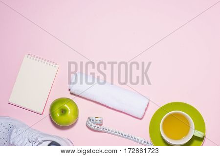 Healthy Concept. Sneakers, Tea, Apple And Measure Tape On Pastel Color Background.
