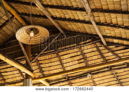 The roof of bamboo leaves and wood. The design of the lamp from a bamboo hat.