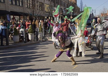 Asheville, North Carolina, USA - February 7, 2016: Spectators watch as people in costume hoot holler and ham it up in the annual Mardi Gras Parade in downtown Asheville, NC