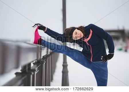 Fitness girl with pink sneakers doing stretching outside at snow winter day, telephoto