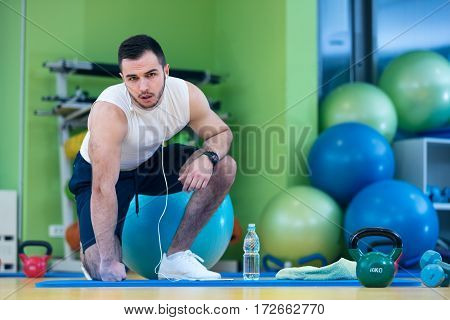 Male athlete kneeling down by dumbbells toweling sweat of his brow