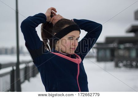 Sporty girl straightens hair during work out fitness at snow winter promenade , telephoto