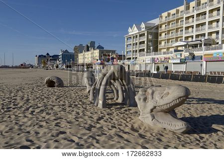 Ocean City, Maryland, USA - October 26, 2016: Tourists walking a long Ocean City boardwalk packed with restaurants shops and other entertainments as viewed from the beach overlooking a dragon sculpture on a sunny autumn day October 26, 2016 in Ocean City,