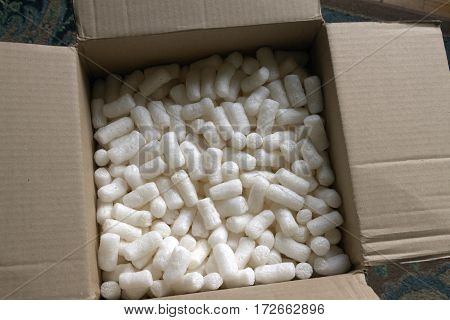 Close up of styrofoam packing peanuts styrofoam popcorn or packing noodles in a cardboard box for cushioning the contents of packages while shipping which are commonly made of expanded polystyrene foam