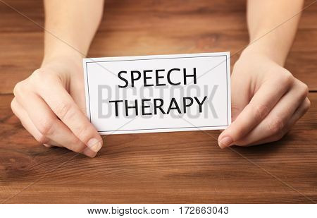 Speech therapy concept. Hands holding card on wooden background