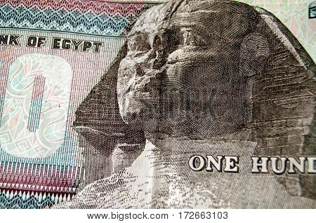 Detail of the one hundred pound banknote from the Egyptian Central bank showing the famous face of the Sphinx of Giza. Used banknote photographed at an angle