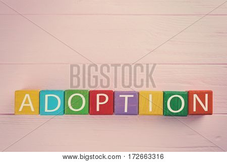 Colorful cubes with word ADOPTION on wooden background