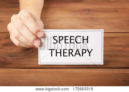 Speech therapy concept. Hand holding card on wooden background