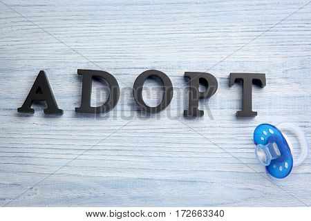 Word ADOPT and passifier on light wooden background