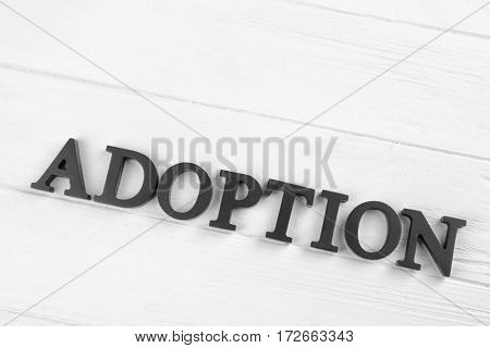 Word ADOPTION made of letters on wooden background. Child custody concept
