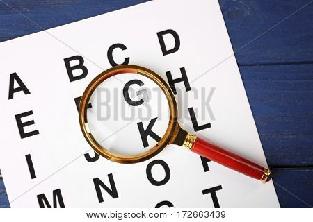 Paper with alphabet and magnifier on blue wooden background