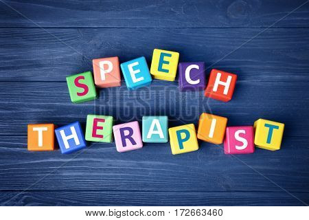 Colourful cubes with text SPEECH THERAPIST on blue wooden background