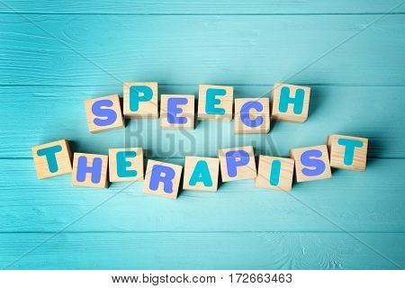 Cubes with text SPEECH THERAPIST on blue wooden background