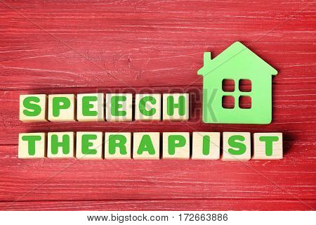 Cubes with text SPEECH THERAPIST on red wooden background