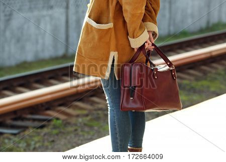 Woman at the railway station with bag