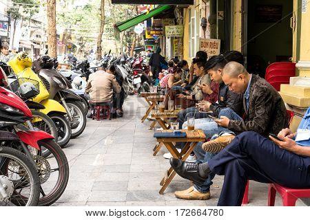 Hanoi, Vietnam - February 17, 2016: People drink coffee on street at old quarter in Hanoi, Vietnam