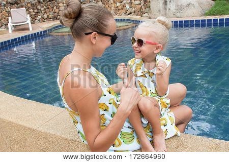 Young mother and her little daughter have fun near the swimming pool.