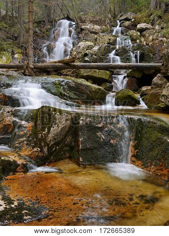 Waterfall and stream in the forest mountain valley