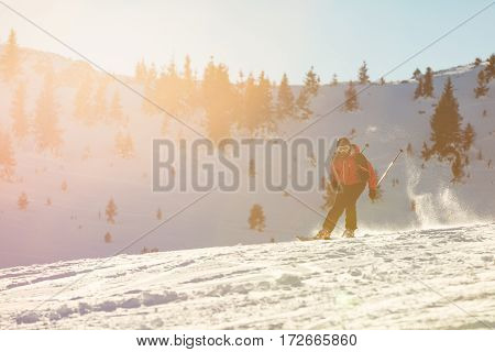 Skier skiing downhill in high mountains against sunset.