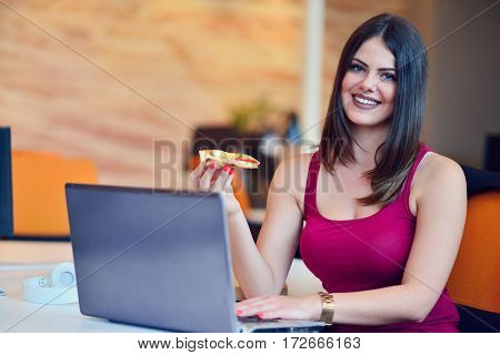 Young buisness woman eating pizza at the office.