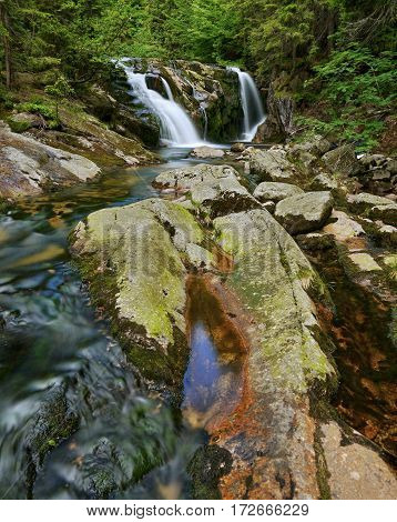 Waterfall and stream in a wooded mountain valley.