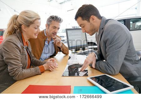 Salesman in car dealership and couple looking at catalogue