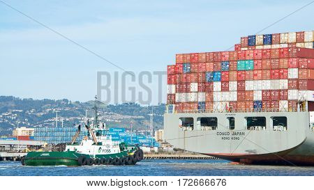 Oakland CA - February 12 2017: A tugboat maneuvers vessels by pushing or towing them. Tugboat LYNN MARIE off the stern of COSCO JAPAN assisting the vessel to maneuver into the Port of Oakland.