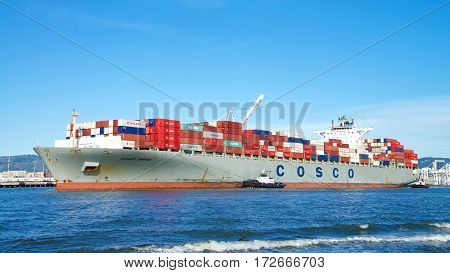 Oakland CA - February 12 2017: COSCO JAPAN entering the Port of Oakland. China Ocean Shipping Company (COSCO) is a government-owned company of the People's Republic of China.
