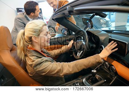 Car seller showing clients convertible car in showroom