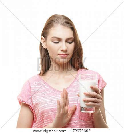 Woman with dairy allergy holding a glass of milk on white background