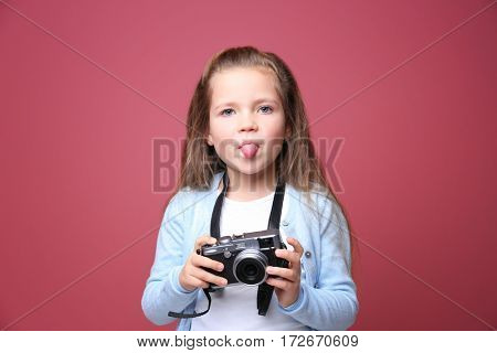 Little girl with vintage camera on color background