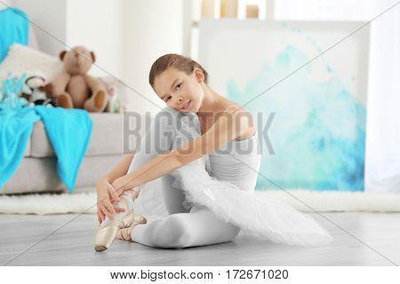 Young beautiful ballerina sitting on floor in room